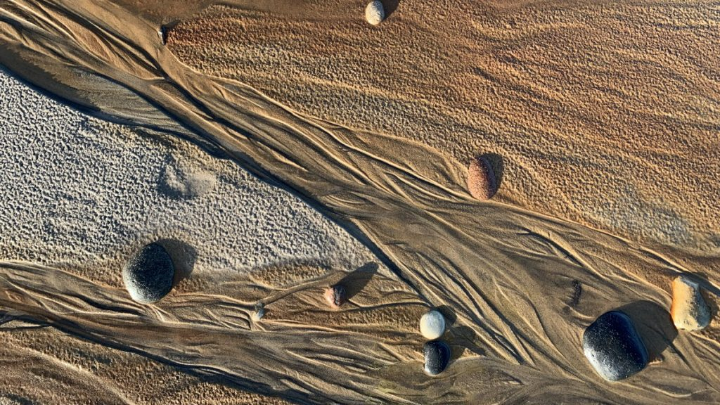 Patterns of sand, stones, water and sun